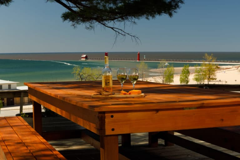 Table on the deck overlooking Lake Michigan, pier, and lighthouse
